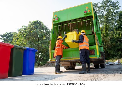 Two refuse collection workers loading garbage for trash removal.
