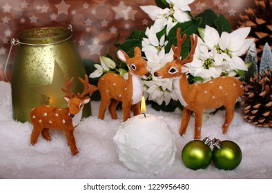 two reindeer with bambi and a white candle in the snow , wooden background with bokeh and a white flower