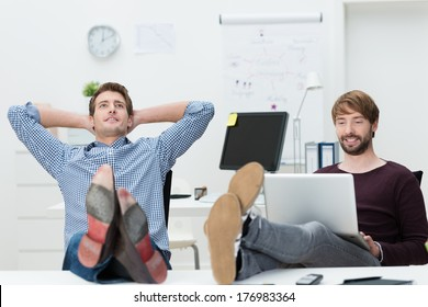 Two relaxed confident young business partners sure of their own success sitting with their feet up on the desk and complacent smiles