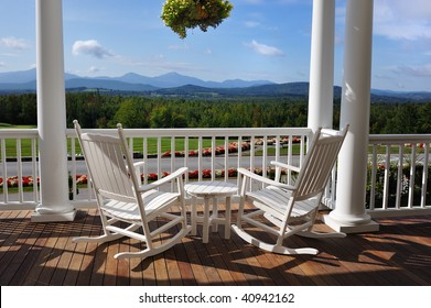 Two relaxing armchairs overlooking peaceful mountain view on porch of luxury resort hotel