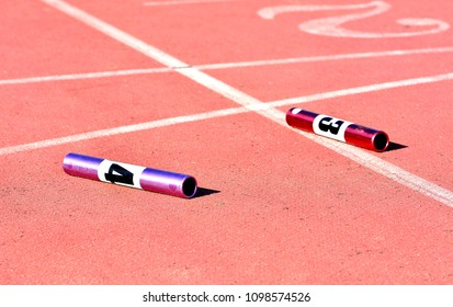Two relay baton on the red track of athletics