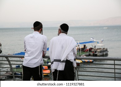 Two religious Jewish men stand on the pier talking in Tiberias, Israel