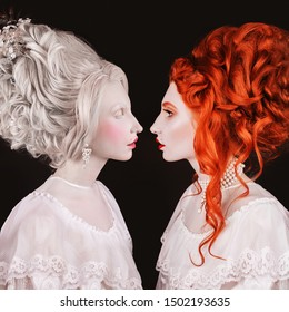Two renaissance queen with hairstyle in white dress. Face profile. Beautiful victorian woman portrait. Renaissance halloween look. Redhead and blonde princess with red lips and hairdo. Beauty face