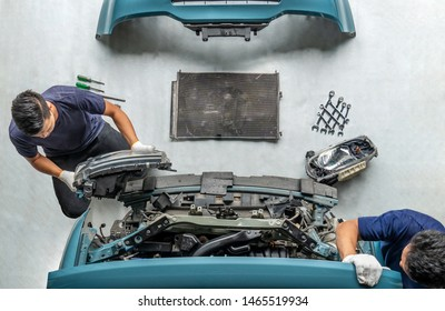 Two repairman mechanics ,Check for damaged cars at the repair station, Maintenance technician is removing the car headlights