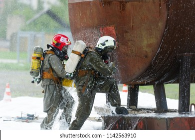 Two rescuers eliminates consequences of chemical accident. Exercises of rescuers at a chemical plant to save industrial facility.