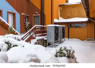 Two residential heat pumps buried in snow