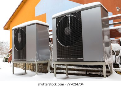Two residential modern heat pumps buried in snow