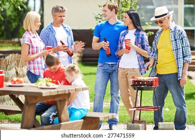 Two restful couple talking outdoors with elderly man frying sausages on grill near by