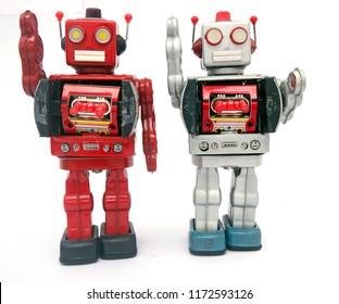 two reto robots waving hello isolated on white