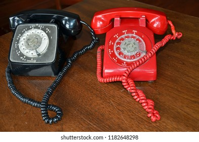 Two retro 60s style rotary dial telephones, one bright red and one shiny black with twisted coil cord with numbers, letters, arrows and dots sitting side by side on a scratched chestnut wooden desk.