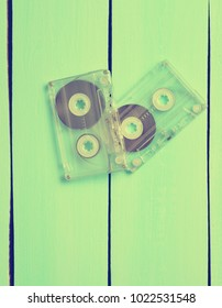 Two retro audio cassettes from 80s on a blue wooden background. Top view.