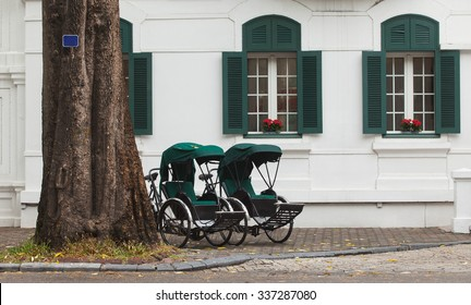 Two retro cyclo parking in front of a five stars French architecture in Hanoi, Vietnam.