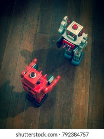 two retro  robots   fight  on a wooden floor shot from above