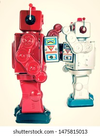two retro robots high five each other isolated on white