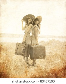 Two retro style girls with suitcases at countryside. Photo in old image style.