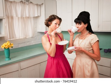 Two retro-styled women drinking coffee in kitchen