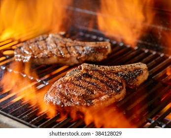 two ribeye steaks grilling on the open flame