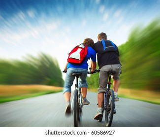 Two riders with backpacks on bikes riding on an rural asphalt roar. Motion blurred