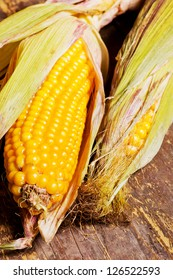 Two ripe corncobs over a wooden background with shallow depth of field