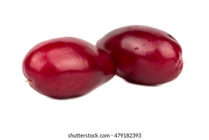 Two ripe cornelian cherry on a white background, close-up