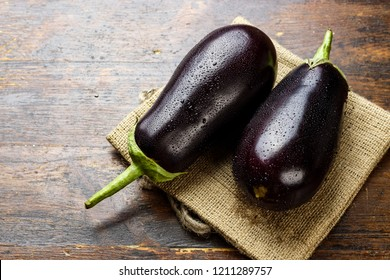 two ripe eggplants on a wooden table, lying on burlap. place for text
