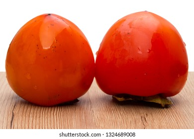 Two ripe persimmons on a table  white background