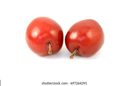 Two ripe red plums with stalks, isolated on a white background