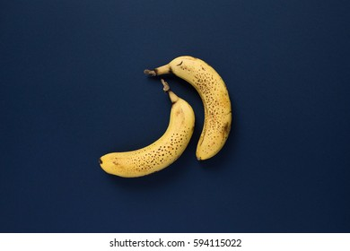 Two ripe speckled bananas on dark blue background. Top view