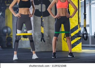 Two ripped women are having strength work out in sport studio. Hey are standing and keeping resistance band on hips. Both ladies are wearing sportswear and trainers