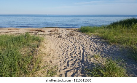 Two Rivers, WI / USA - July 04 2017: White sandy beach covered in footprints & stroller tracks framed by tall grasses leading to a quiet spot on Neshotah Beach on the Great Lake Michigan shore.