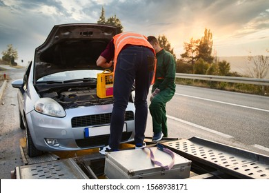Two road assistant workers in towing service trying to start car engine with jump starter and energy station with air compressor. Roadside assistance concept.