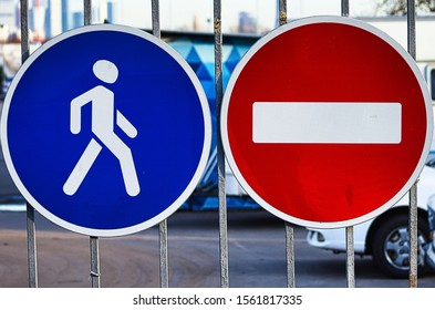 two road signs nearby on the fence, no entry and pedestrian zone