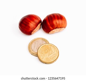 Two roasted chestnuts in a pile, isolated on white background. One euro and twenty cents coins, selling seasonal street food, chestnuts business conсept.
