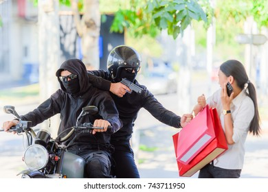 Two robbers ride on the motorbike snatching a bag from an asian young woman walking alone