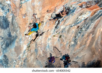 Two Rock Climbers moving on high vertical Wall in orange and blue colors while Group of other Athletes belaying them from far below Ground