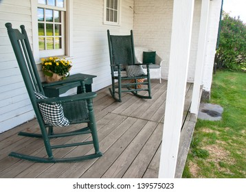 Two rocking chairs invite one to sit a while on this old porch.