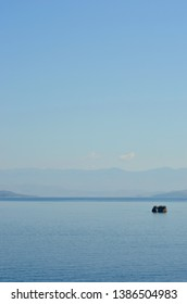 Two rocks form a small tree-covered island dwarfed by the expanse of a large bay. A blue-tinged mountain range is in the distance. The sky is a pale blue with faint white clouds.