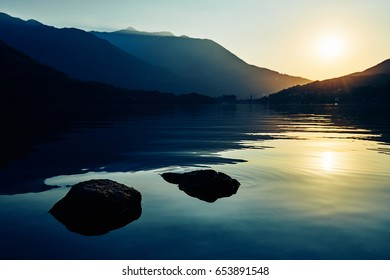 Two rocks on a calm mountain lake at sunset in Italy