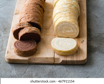 Two rolled cakes, chocolate and milky vanilla, on a cutting board. Concrete background
