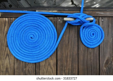 two rolls of blue cord rope securing boat to dock