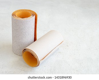 Two rolls of extra coarse and super fine aluminum oxide sandpaper on a white rough textured background. Abrasive paper for dry sanding. Processing wood and metals, furniture production. Close-up.