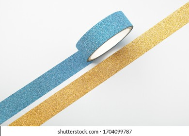 Two rolls of glitter tape and parallel strips on white background