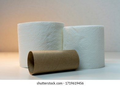 Two rolls of white toliter paper (TP) in different sizes with empty cardboard cylinder roll lying on its side in foreground.
