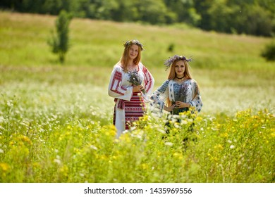 Two Romanian girls in traditional costume with lavender flowers in a field