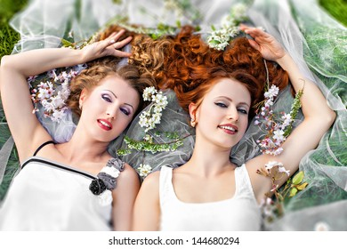 Two romantic girls lying in spring blossom