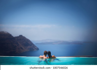 two in a romantic journey. Lovers swim in the pool overlooking the sea. Blue water and sky. View of the mountains and volcano islands