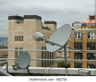 Two rooftop satellite dishes, poised to receive signals.  New York City.