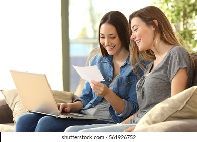 Two roommates checking bank mails on line with a laptop sitting on a couch in the living room at home