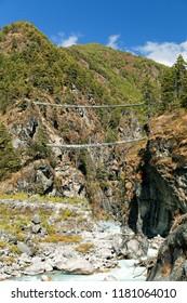 Two rope hanging suspension bridges in Nepal Himalayas under Namche Bazar above Dudh Koshi Nadi river, Mount Everest base camp trek