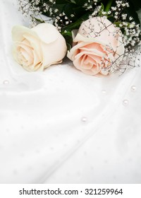 Two roses on a white silk background